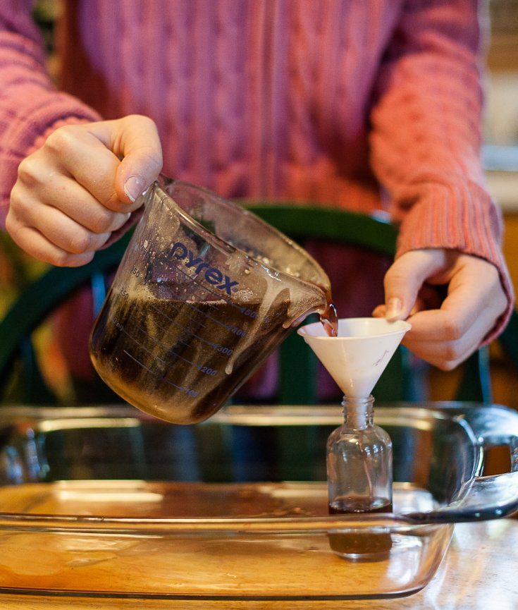 woman pouring elderberry syrup into funnel